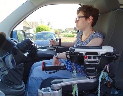 Beth uses a Single Arm to access her Lightwriter when driving.
