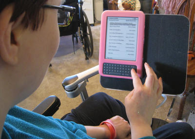 Kat uses 3 devices on her chair: a Kindle, a laptop and a speech device.