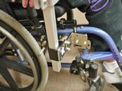 L-angle extension plate adjusts the position of the Wheelchair Bracket to allow footrest removal, brake activation and propulsion..