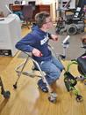 This young man has a Single Arm on his wheelchair, and a Tilt'n Turner on his walker. He can remove and transfer his device from one to the other.