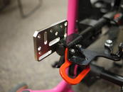 Close-up of the attachment of the Adapter Plate, sandwiching the frame, tie down and seat pan.
