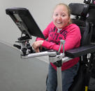 The ability to access something from either a standing or seated position in a standing wheelchair requires attachment to the armrest.