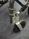Caster wheel bolted to wheelchair frame