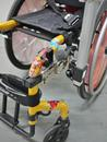 Attach a Bridge clamp to both the horizontal and vertical tube sections, on either side of the bend. Notice the use of the Adapter Plate and L-Angle Extension to move the Wheelchair Bracket to avoid interfering with the brakes.