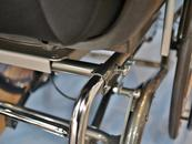 Note the intersection of the tube beneath the seat with the side frame, and create a bridge clamp. Attach the Adapter Plate so it is horizontal. Attach an L-Angle to it, providing a vertical face to attach a Wheelchair Bracket.